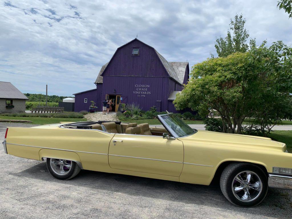 A vintage car parked in front of a winery